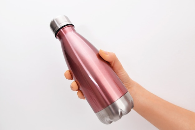 Close-up of female hand, holding reusable steel stainless eco thermo water bottle,  on white wall. be plastic free. zero waste.
