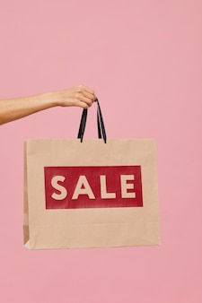 Close-up of female hand holding sale shopping bag against the pink background