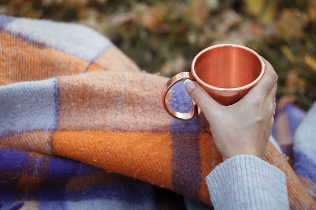 Close-up female hand holding a shiny copper mug with tea