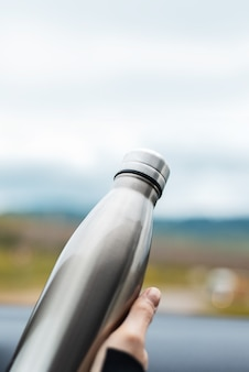 Close-up of female hand holding a steel reusable thermal water bottle on wall of sky.