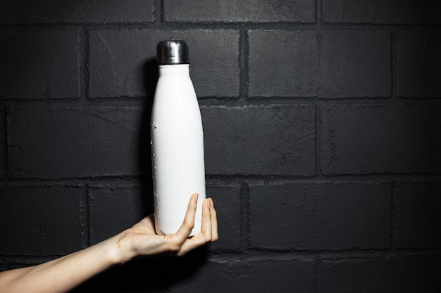 Close-up of female hand, holding a steel thermo water bottle of white color, on the background of black brick wall.