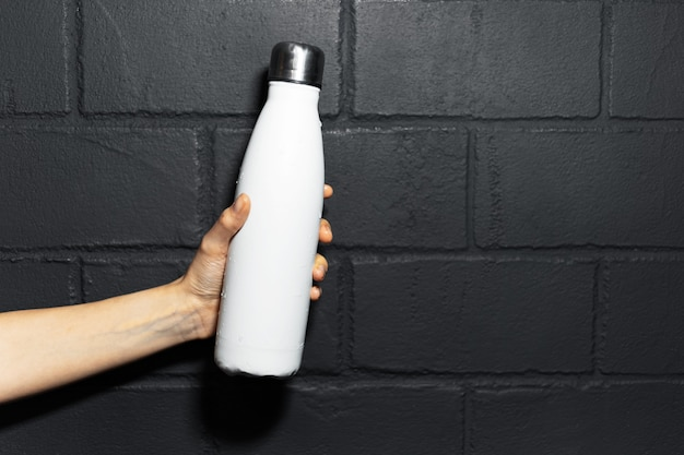Close-up of female hand, holding steel thermo water bottle of white color, on the background of black brick wall.