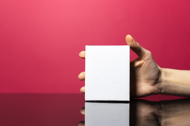 Close-up of female hand holding white paper card with mockup on pink coral surface