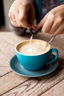Close-up of female hand pours sugar into coffee over wooden surface
