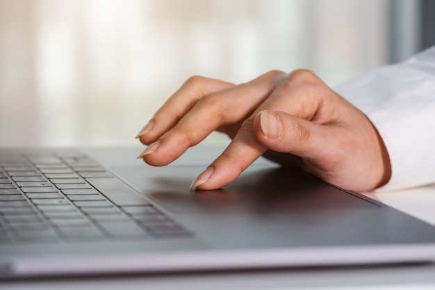 Close-up female hand touching touchpad on a laptop computer