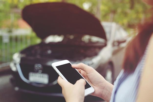 모바일 스마트 전화를 사용하여 여성의 손을 닫습니다 전화 자동차 정비사