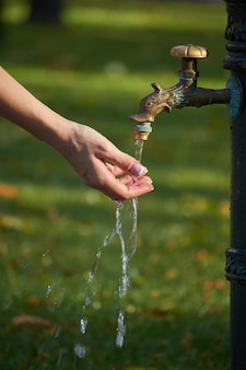Close-up of female hand under water from an old-style column with drinking water in an autumn park, selective focus