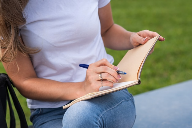 Close up of a female hand who writing in a notebook while sitting on the street in the park.