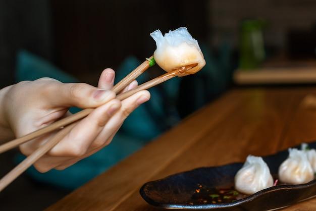 箸で熱い中国の餃子で女性の手を閉じる