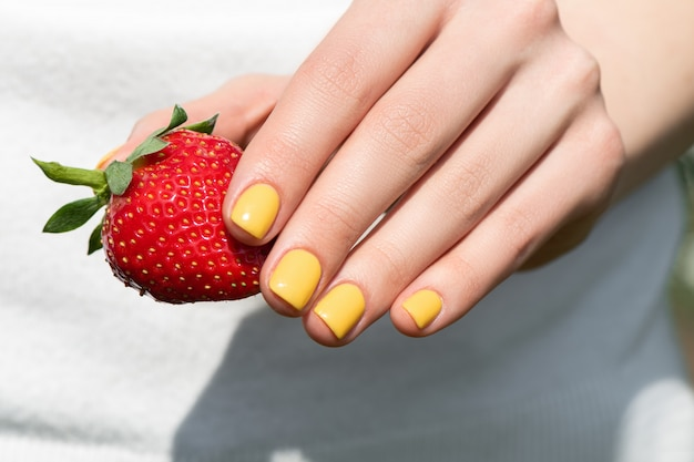 Close up of female hand with pretty yellow nail design manicure holding ripe strawberry.