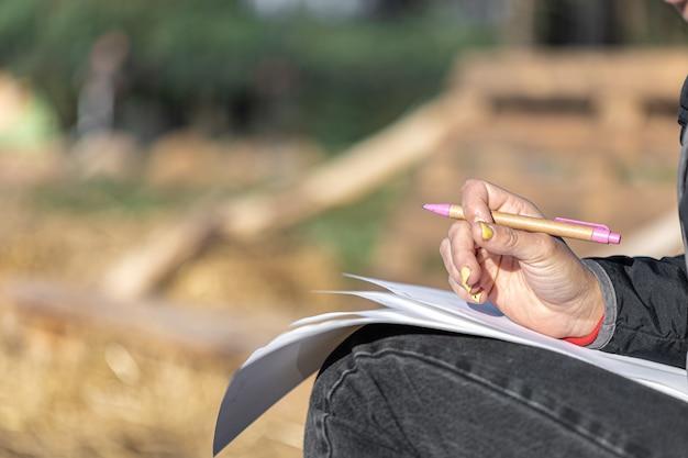 Il primo piano di una mano femminile con una manicure gialla tiene una penna e fogli di carta su uno sfondo sfocato all'esterno, copia spazio.