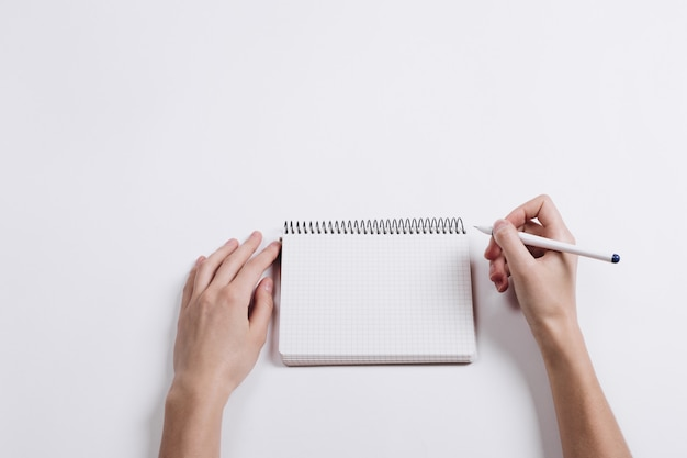Close-up of female hand writing pen in a blank notebook