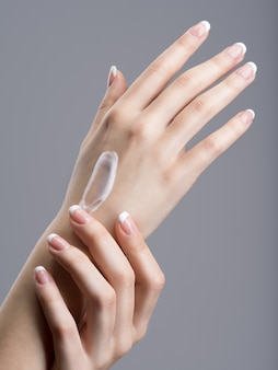 Close-up female hands apllying hand cream