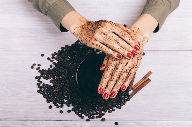 Close-up of female hands apply coffee scrub