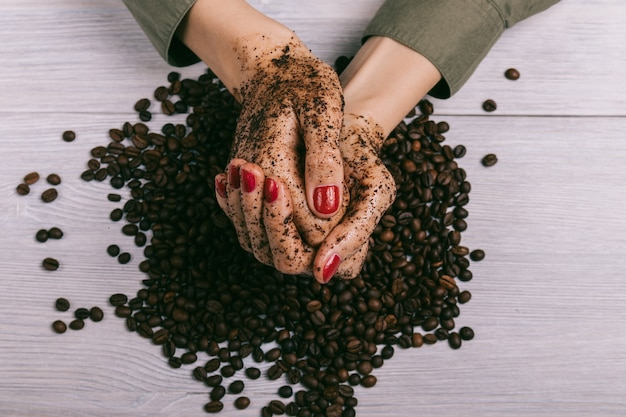 Close-up of female hands coated with scrub and coffee beans