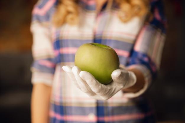 Chiuda in su delle mani femminili in guanti che tengono mela verde, cibo sano, frutta