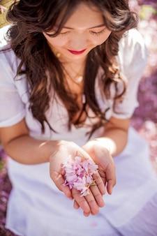 閉じる。女性の手はピンクの花の花びらを持っています。白いドレスを着た若い美しいアジアの女性が花の咲く公園を歩きます。