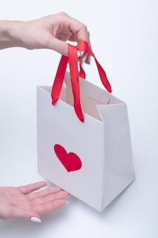 여성의 손을 닫고 테이크아웃을 위한 하트 모양의 기호가 있는 흰색 가방을 들고
