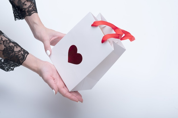 Close up female hands hold white bag with a symbol in the form of a heart for takeaway