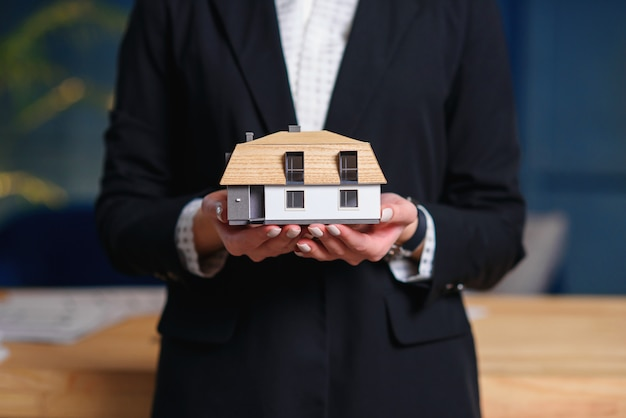 Close up of female hands holding 3d model of house.