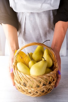 Close-up of female hands holding a basket with fresh organic pears on a white