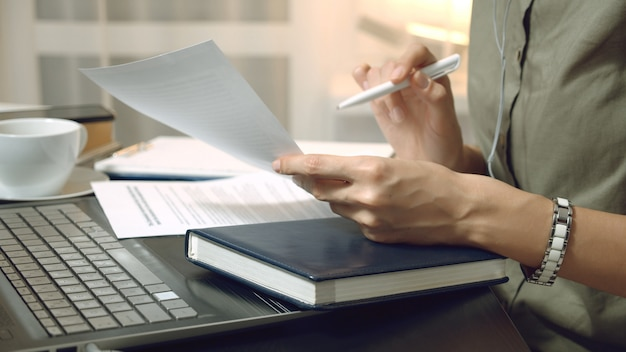 Close up of female hands holding a contract or financial report and taking notes at the workplace