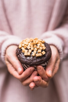 Close-up of female hands holding cup cake with caramel candies toppings