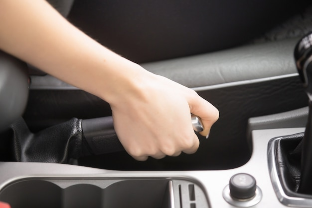 Close-up of female hands holding a handbrake