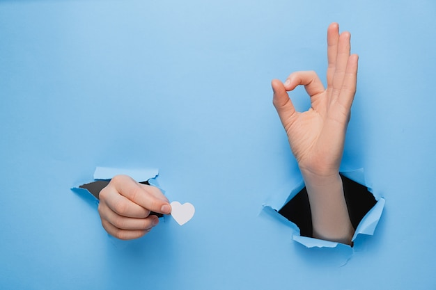 Close up of female hands holding little white hearts through and shows an ok sign a torn blue paper wall.