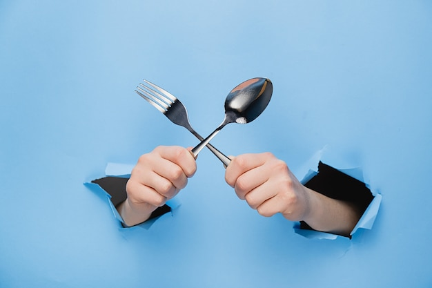 Close up of female hands holding spoon and fork through torn blue paper wall.