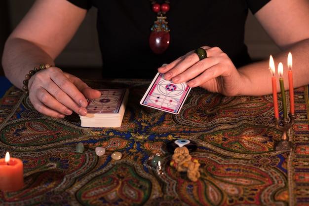 タロットカードを持っている女性の手を閉じます。占い師。魔術