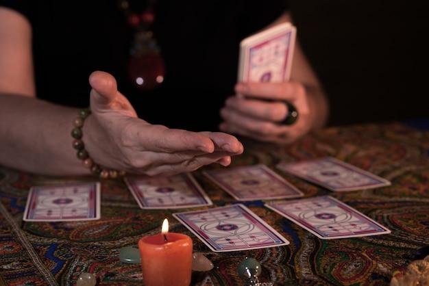 타로 카드를 들고 여성 손을 닫습니다. 점쟁이. 요술