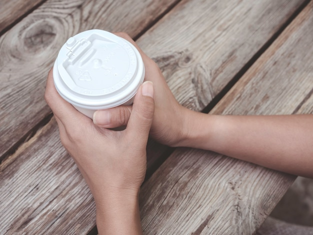 Close up female hands holding a white coffee paper cup on wooden table. young woman drinking coffee from disposable cup.