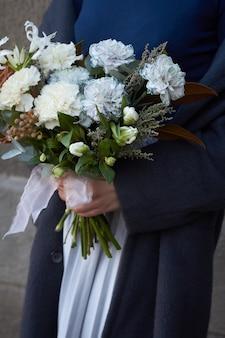 Крупным планом женские руки держит белый тонированный букет в винтажном стиле на открытом воздухе на серой стене