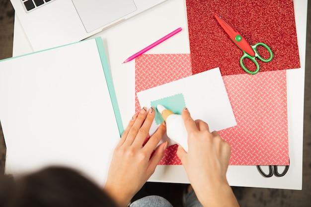 新年とクリスマスのグリーティングカードを作る女性の手をクローズアップ