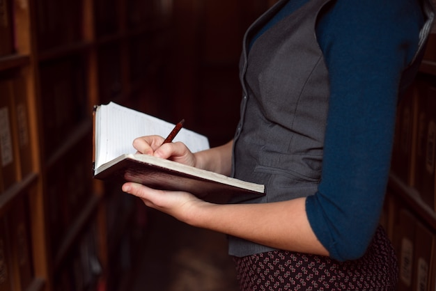Close up of female hands making notes in notebook