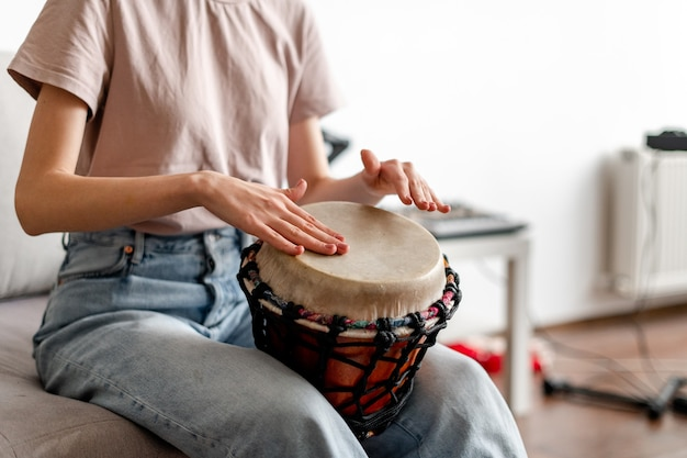 Close-up female hands playing djembe indoors
