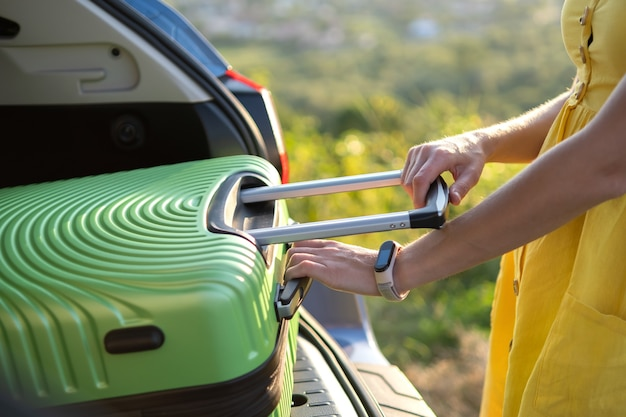 Close up of female hands taking green suitcase from car trunk. travel and vacations concept.