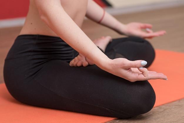 Крупным планом женские руки, которые сидят в позе лотоса и демонстрируют жест дзен
