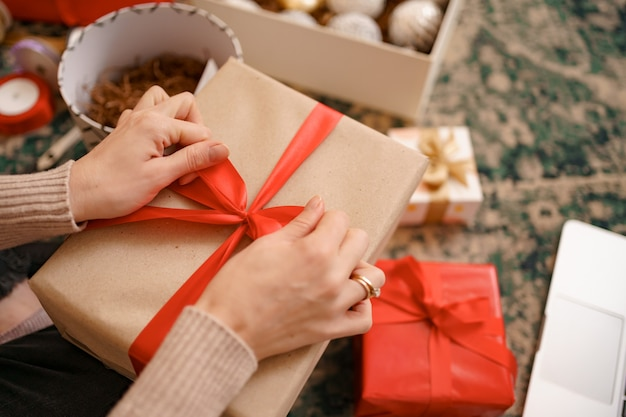 Close up female hands tying a red ribbon bow on a craft gift box.