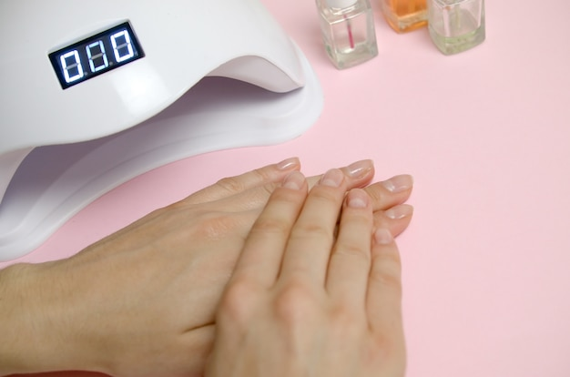Close up female hands with beautiful trendy transparent manicure on white table background