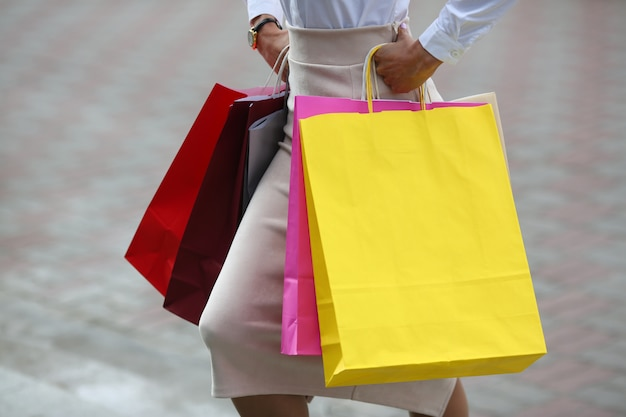 Close-up of female hands with colorful packages walking down street. beautiful woman wearing business style clothes. fashion and shopping concept.
