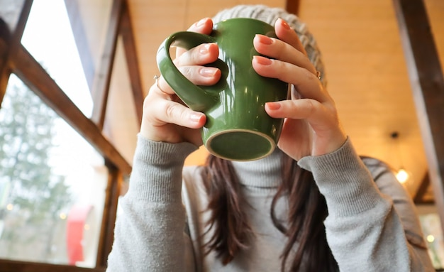 Close up of female hands with a drink mug. a girl in a gray sweater holds a cup of coffee or cocoa in a cafe at the table and looks out the window. hot drink. a cozy photo with a blurry background