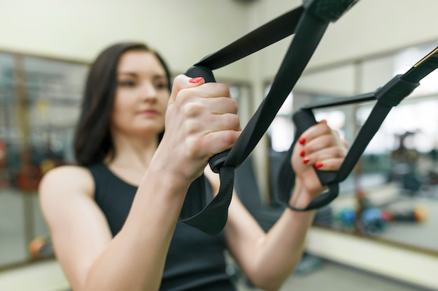 Close-up female hands with fitness straps in gym