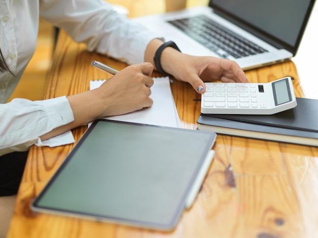 Крупным планом женские руки с ноутбуком, планшетом и калькулятором, рассчитывающим расходы компании
