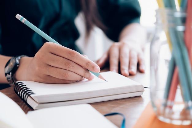 노트북에 쓰는 펜으로 여성 손을 닫습니다.