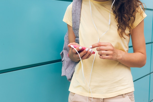 Close-up of female hands with white manicure holding pink mobile phone and headphones outdoors