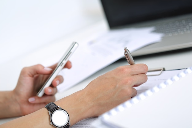 Close-up of female hands working with documents at the office. woman writing something and looking at mobile phone screen
