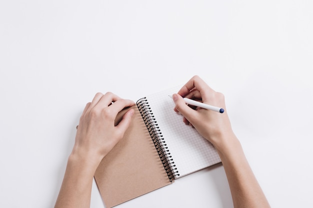 Close-up of female hands writing in notepad with a pen on a table