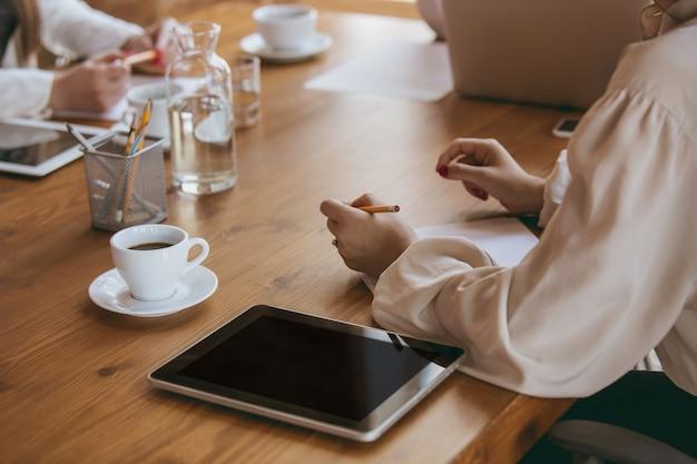Закройте вверх женские руки написание заметок во время творческой встречи, обсуждения, проекта, работающего в офисе. понятие финансов, бизнеса, женской силы, включения, разнообразия, феминизма. выглядит счастливым и внимательным.